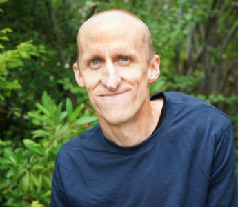 a portrait of Andy Jackson, a bald man with pale skin and blue eyes. He is wearing a navy blue shirt