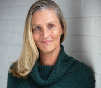 A portrait of Anna George, a white woman with long blonde hair and light eyes. She is wearing a turquoise jumper against a white background