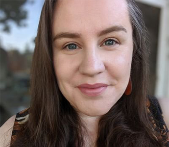 A white woman with long brown hair streaked with grey smiles directly at the camera.