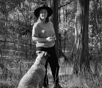 A black and white portrait of Bonny Cassidy, a woman with pale skin standing with her dog in front of a tree. She is wearing a sun hat and a short sleeved shirt