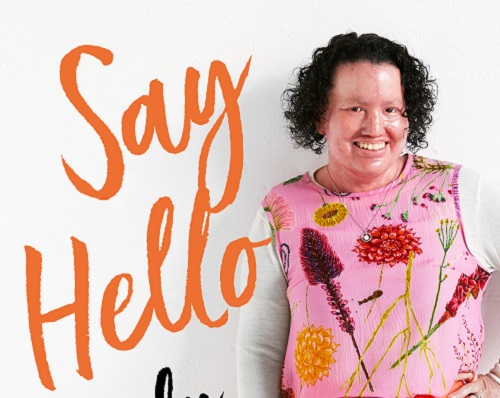 Carly Findlay - a woman with a red face and curly brown hair wearing a pink floral top against a white background and text in orange that reads 'Say Hello'