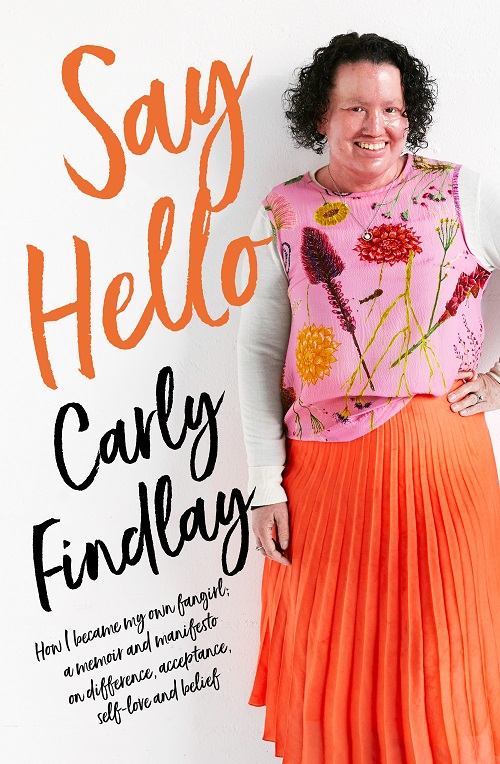 a woman with a red face, brown curly hair, in a pink floral top and orange skirt. Orange text reads 'Say Hello', and black text reads 'How I became my own fangirl; a memoir and manifesto on difference, acceptance, self-love and belief.'