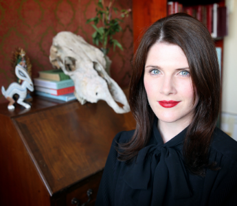 A portrait of Chloe Wilson, a woman with pale skin and blue eyes. She has long dark hair and is posing in front of an animal skull