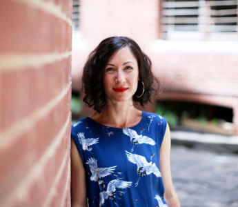 A portrait of Emily Brewin, a woman with pale skin, dark hair and dark eyes. She is wearing a blue top and leaning against a brick wall