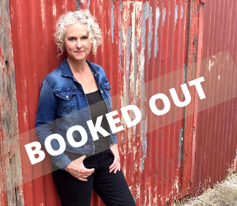 a portrait of Emma Viskic, a woman with pale skin and grey, curly hair. She is wearing a denim top and leaning against a distressed red gate.