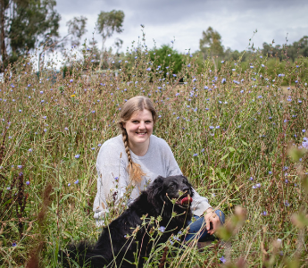 A portrait of Eliza Henry-Jones, a woman with pale peach skin and blonde hair. She is sitting in a field of flowers with her dog