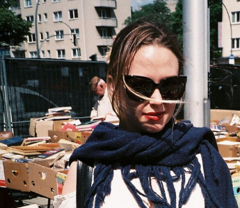 A portrait of Ellena Savage, a woman with pale skin and brown hair. She is wearing large sunglasses and stands in an open-air book bazaar