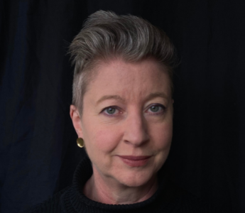 A portrait of Emily Collyer, a woman with medium peach skin and short grey hair. She is standing against a black background.