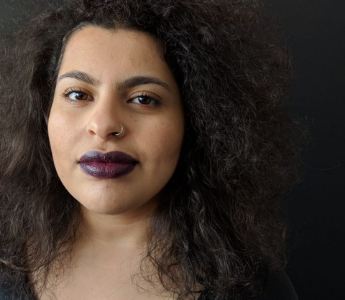 A portrait of Hella Ibrahim, a woman with light brown skin and long dark hair. She has brown eyes and is wearing a purple lipstick
