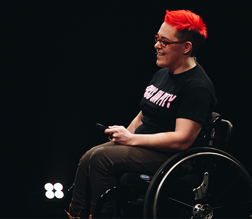 A photo of a woman with bright red hair in a wheelchair. Her T-shirt reads 'Piss on Pity'