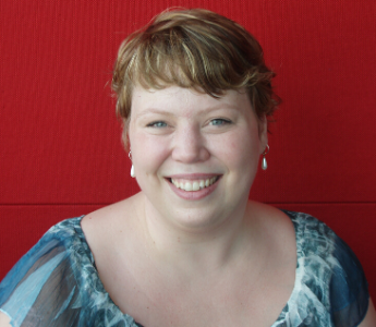 A portrait of Kate Cuthbert, a white woman with short blonde hair and blue eyes. She is smiling in front of a red background