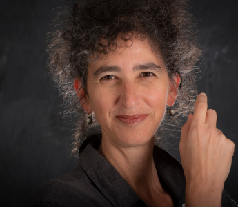 A portrait of Laurel Cohn, a woman with medium peach skin, dark curly hair, and dark eyes. She is smiling and lightly back-lit