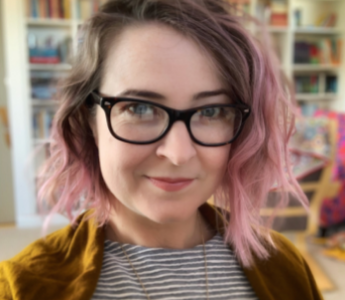 a portrait of Lili Wilkinson, a woman with pale peach skin and pink hair. She is smiling and wearing glasses