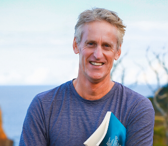 a portrait of Mark Smith, a man with medium peach skin and light hair. He is standing in front of the ocean.