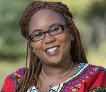 A portrait of Rafeif Ismail, a woman with medium brown skin and brown, braided hair. She is smiling and wearing glasses.