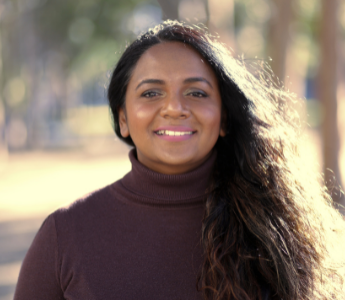 A portrait of Sangeetha Thanapal, a woman with medium brown skin and long dark hair. She is smiling and has an out-of-focus landscape scene behind her