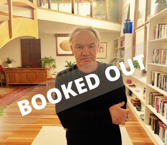 A portrait of Tony Birch, a man with medium peach skin and white hair. He is standing in a lounge room and has a slight smile on his face. There is a banner reading 'booked out' across his chest