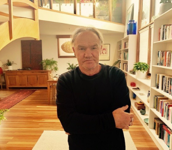 A portrait of Tony Birch, a man with medium peach skin and white hair. He is standing in a lounge room and has a slight smile on his face