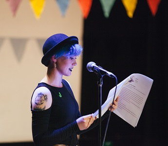 A photograph of a young person reading a story into a microphone