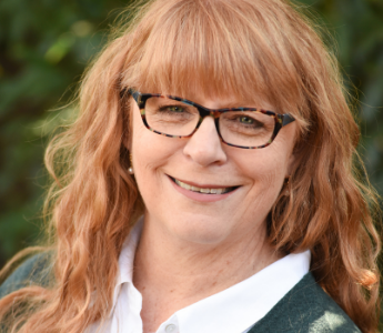 A portrait of Victoria Purman, a woman with medium peach skin and light red hair. She is smiling and wearing glasses